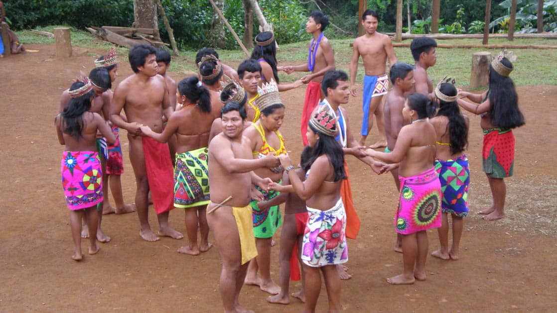 a group of indigenous people in bright garments stand holding hands in a dirt section of the jungle on the panama family adventure land tour