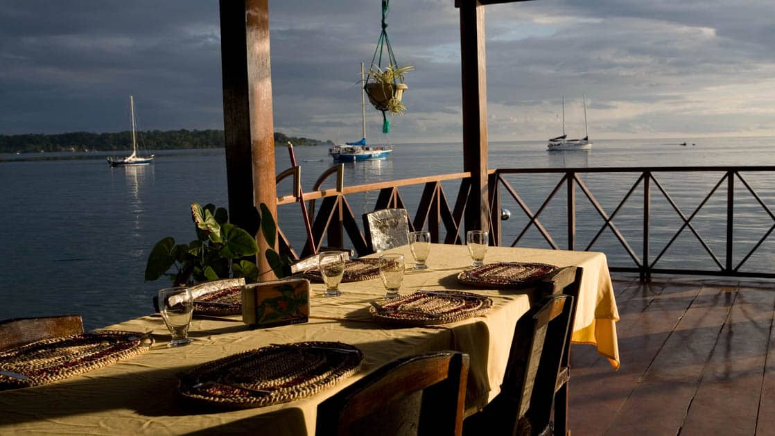 a table set on an outdoor deck with a wooden railing next to it, overlooking the waters of boca del toro with a small ship in the background