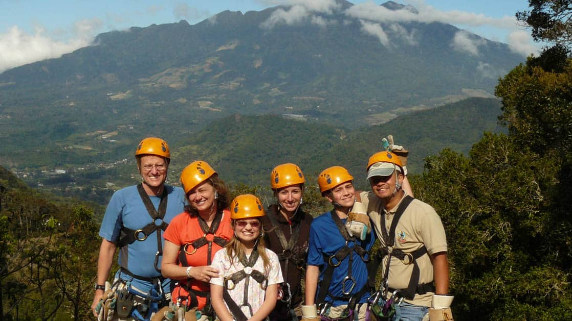 group of adventure travelers with harnesses and orange helmets with mountains in the background on the panama family adventure land tour
