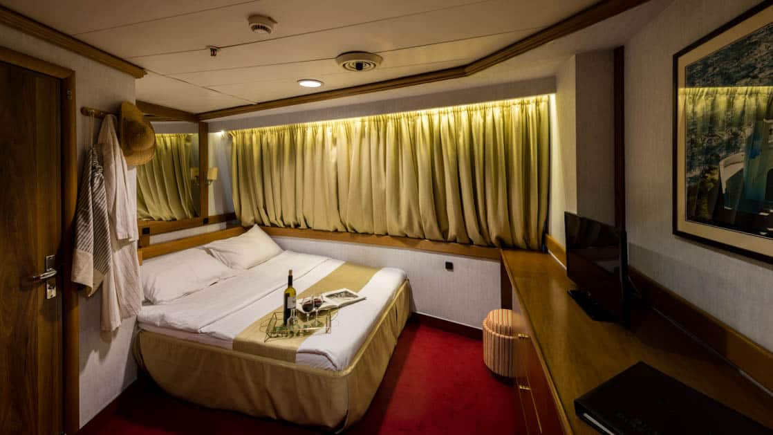 panorama luxury yacht cabin with a double bed and curtains over the large window