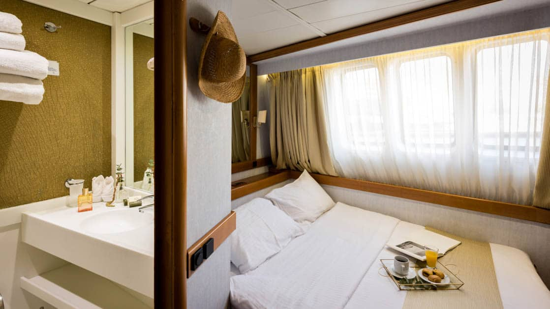 panorama luxury yacht cabin with large bed, large window and a hat hung on the wall