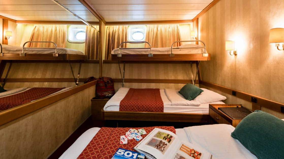 panorama luxury yacht room with 3 beds and small windows at the top of the wall
