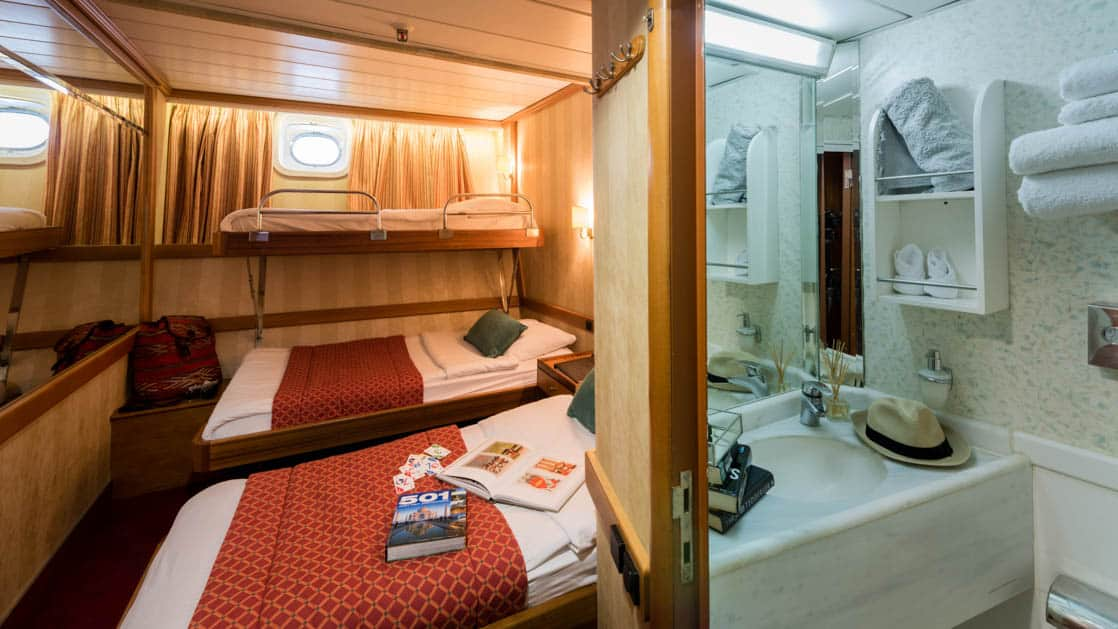 panorama Mediterranean luxury yacht cabin with three beds with windows above them and a white bathroom