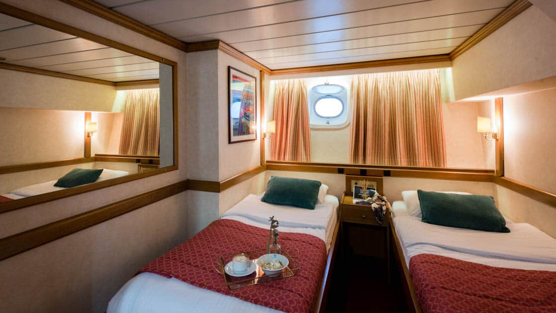 panorama Mediterranean luxury yacht room with 2 beds and a porthole above them