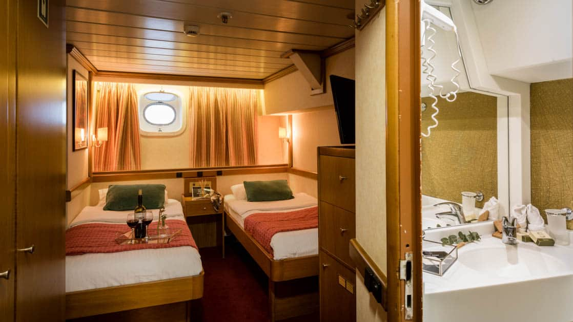 panorama Mediterranean luxury yacht room with 2 beds, a porthole, and a lit bathroom