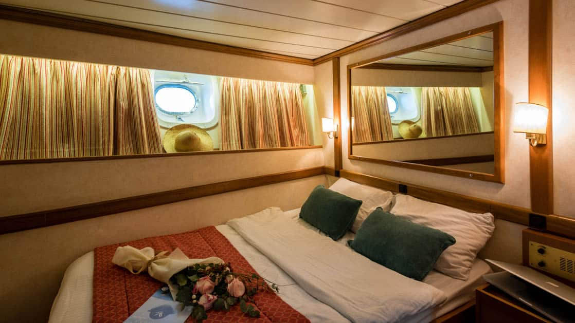 panorama Mediterranean yacht cabin with large bed, mirror above the bed and porthole window