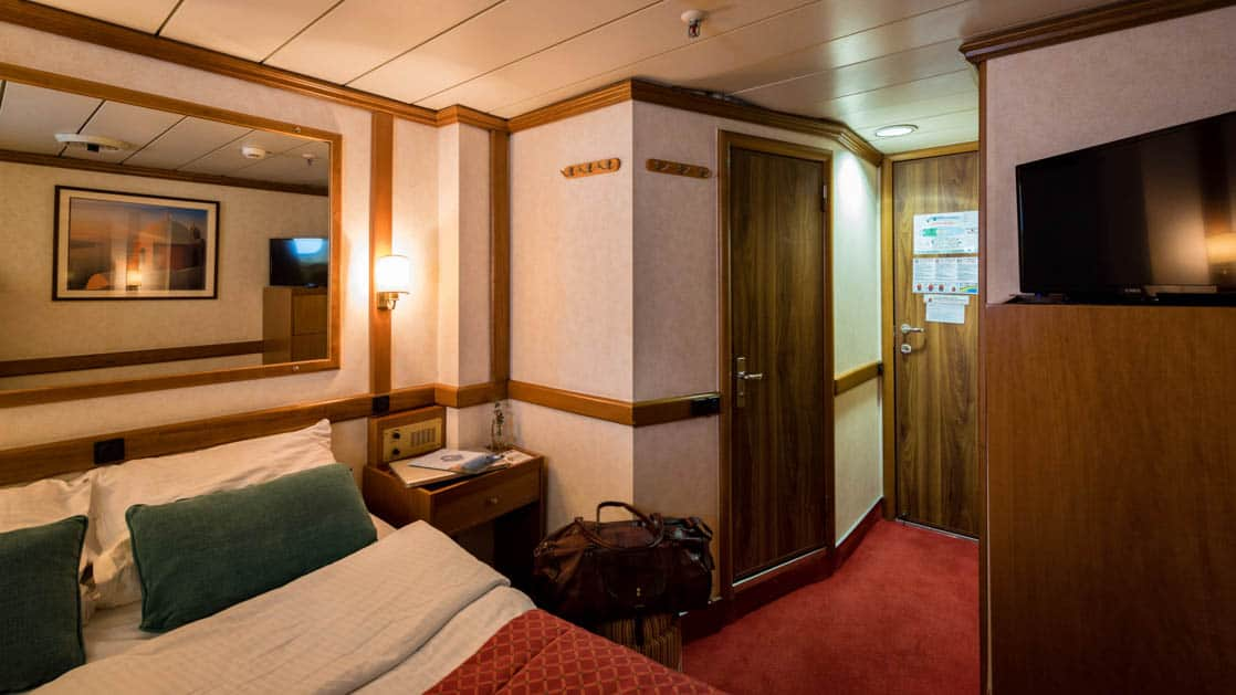 panorama Mediterranean yacht cabin with two beds and a door leading to a bathroom
