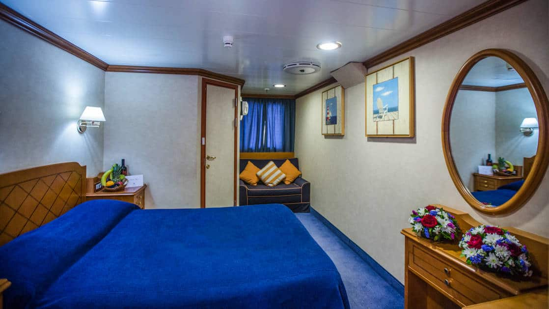 Double bed with mirror and wine and snacks on bed side table with small window aboard Panorama II
