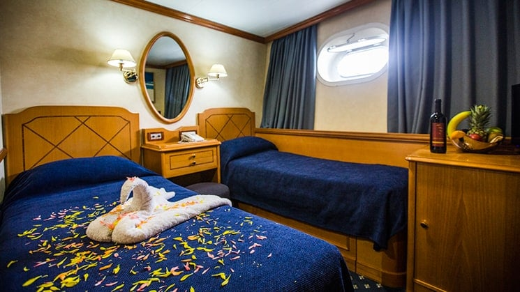 Two twin beds with towel made into a swan, mirror, porthole window and curtains aboard Panorama II.