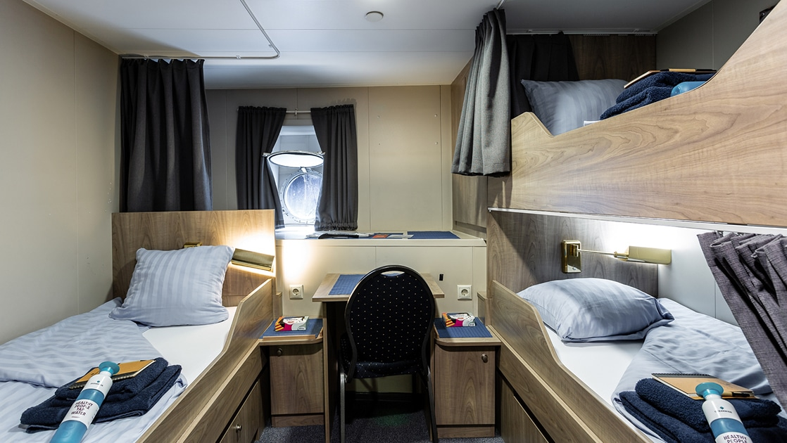 room with 3 beds and a porthole aboard Plancius Antarctica small ship