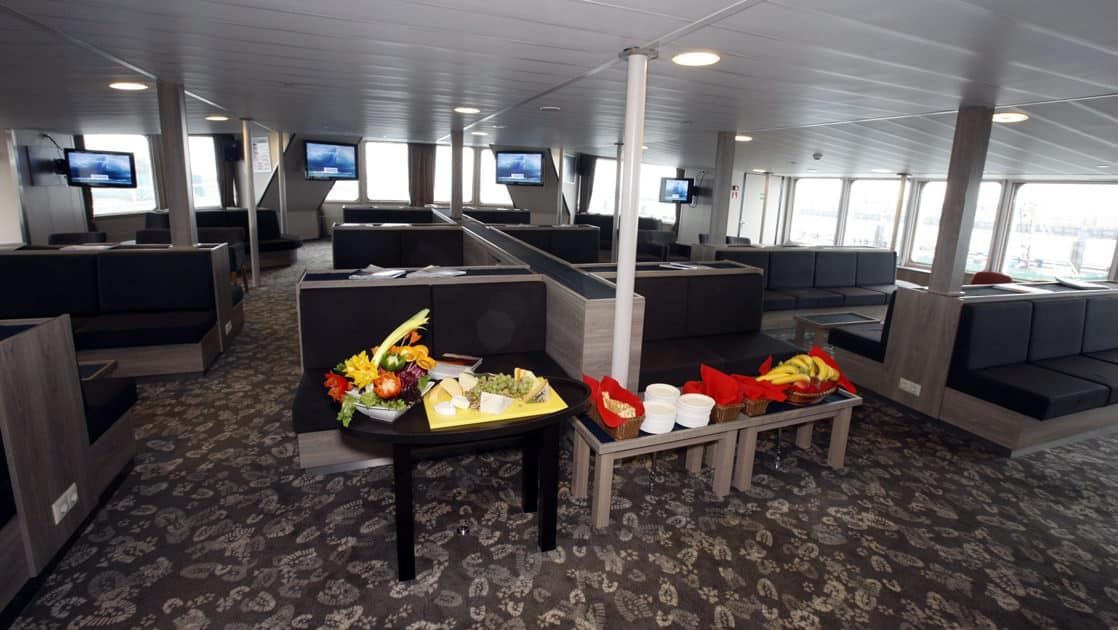 plancius antarctica expedition ship lounge with couches and tables filling the room and windows on the end