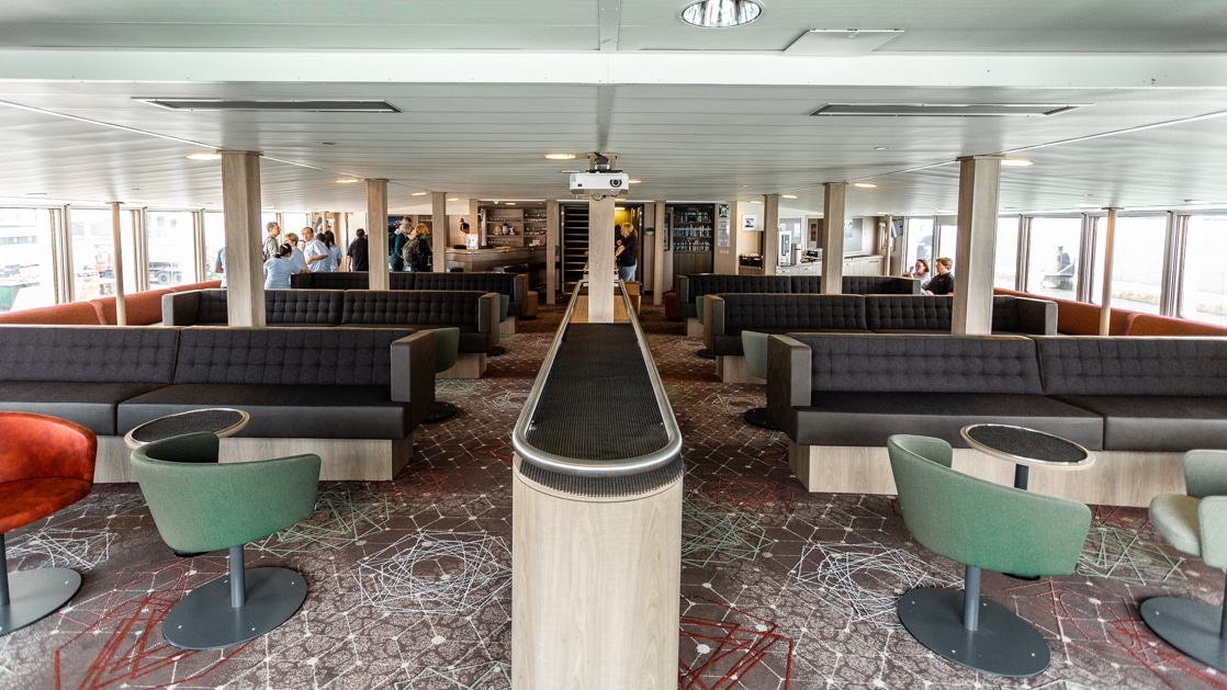 plancius polar expedition ship lounge with couches and tables filling the room and windows on the end