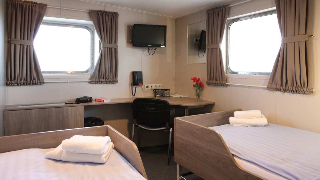 Twin Deluxe cabin with 2 windows and a table aboard Plancius polar vessel