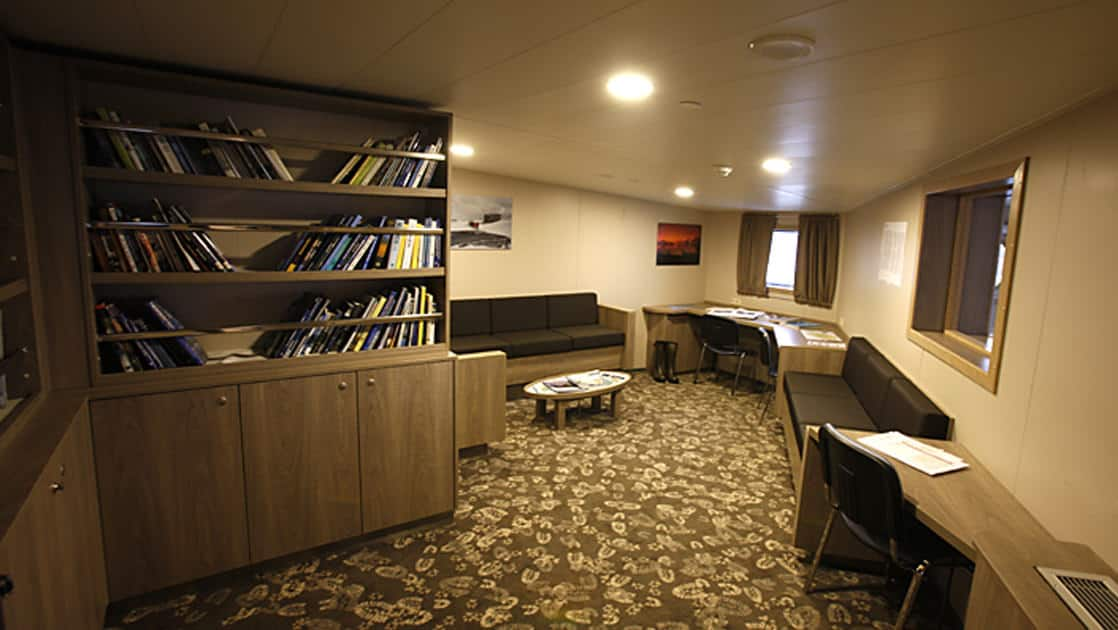 plancius antarctica expedition ship library with patterned carpet and a bookshelf