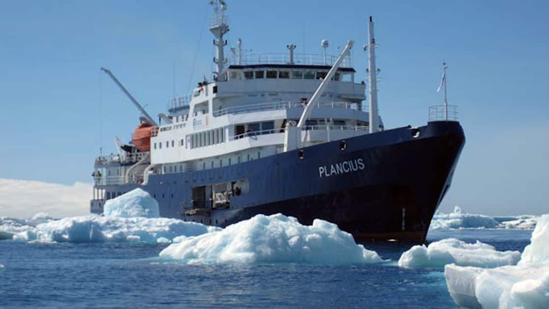 Plancius small ship cruising in Antarctica with sea ice around it