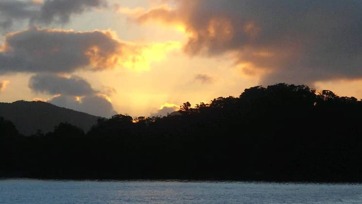 a beautiful cloudy sunset in preservation inlet new zealand with an illuminated area in the middle