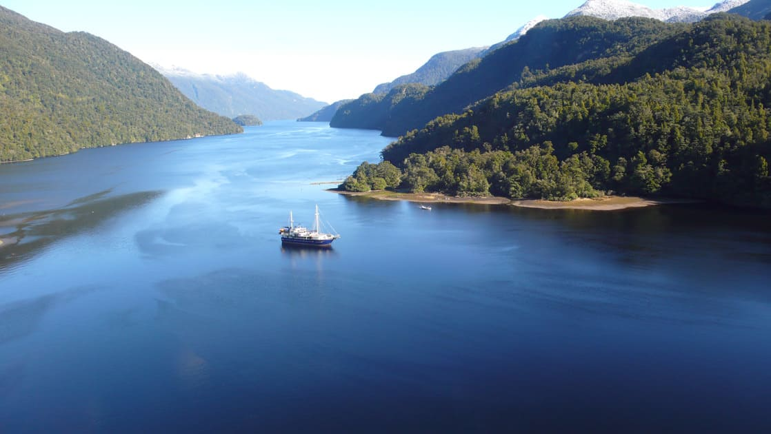 a sunny day on the preservation inlet discovery cruise with the milford wanderer small ship anchored in the distance and lush mountains jutting out along the way