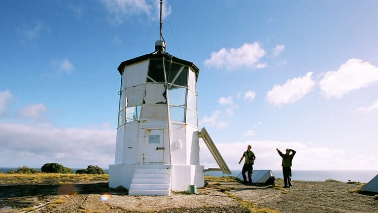 two travelers stand next to a white lighthouse on a sunny day in new zealand, with the ocean barely visible beyond them
