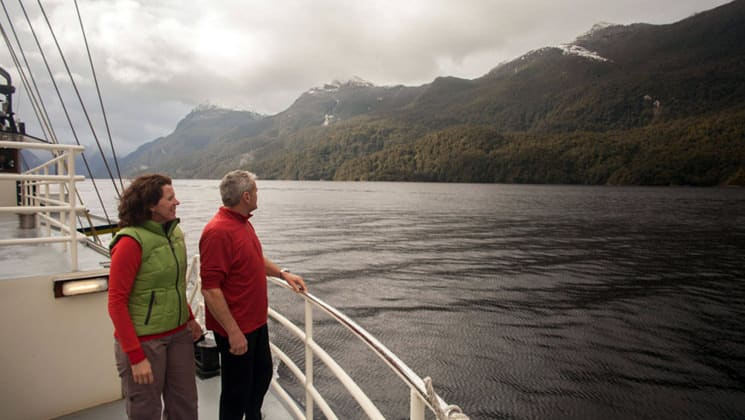 two passengers stand on the deck of the milford wanderer small ship looking out at the water and mountains on the preservation inlet discovery new zealand cruise