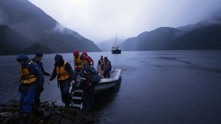 travelers exiting a zodiac skiff on a misty day in new zealand during the preservation inlet discover cruise, with the milford wanderer small ship anchored behind them and sheer mountains farther in the distance