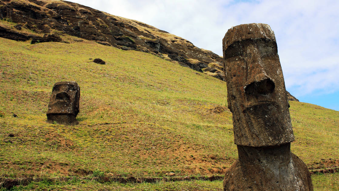 Two Rapa Nui Moai statues on a green hill.