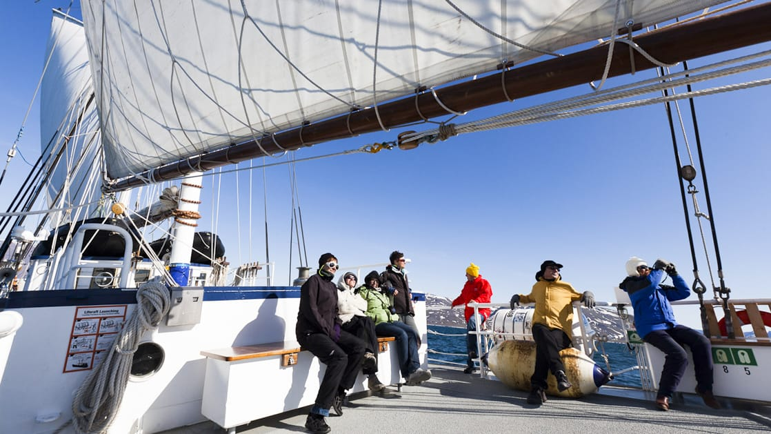 travelers standing on the deck of the Rembrandt van Rijn arctic small ship with the sail up on a sunny day