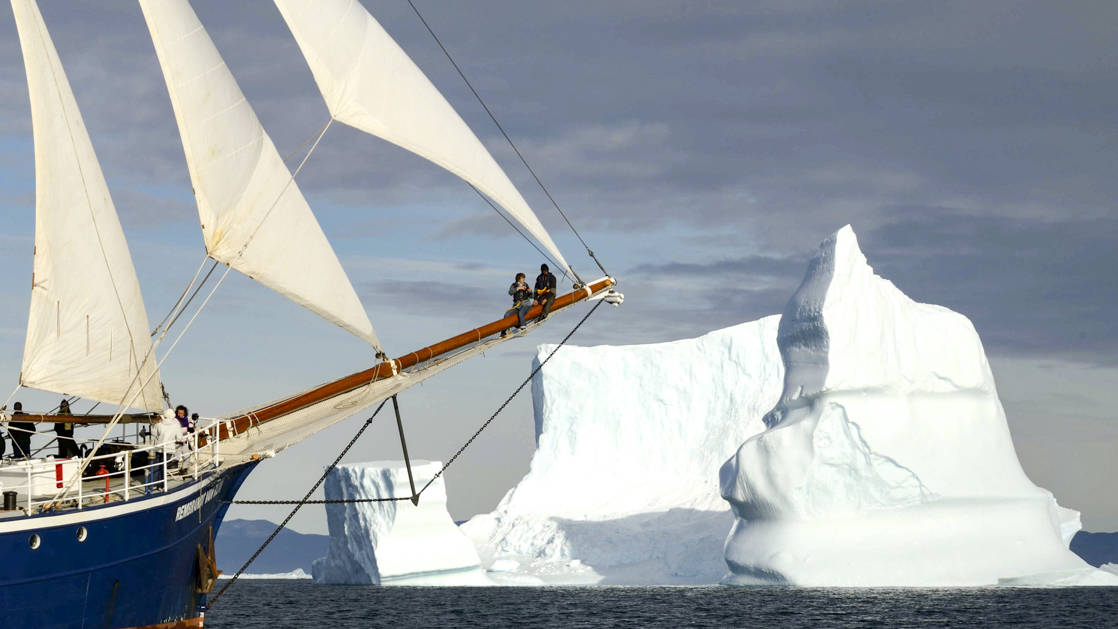 the front of the Rembrandt van Rijn small ship in the arctic with an iceberg behind it