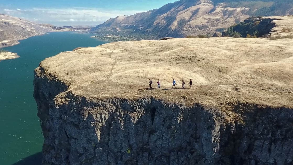 adventure travelers hiking on the edge of a cliff overlooking the columbia river in the pacific northwest on a sunny day