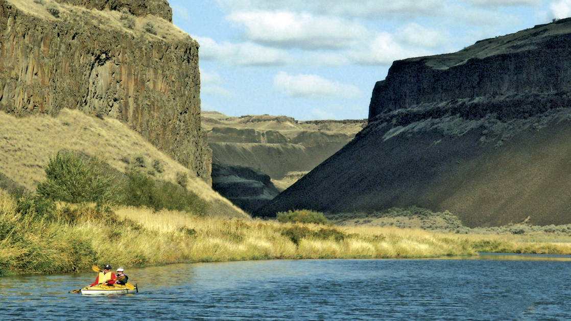Rivers of Adventure & Wine small ship cruise travelers paddling in a yellow kayak in a canyon in the pacific northwest