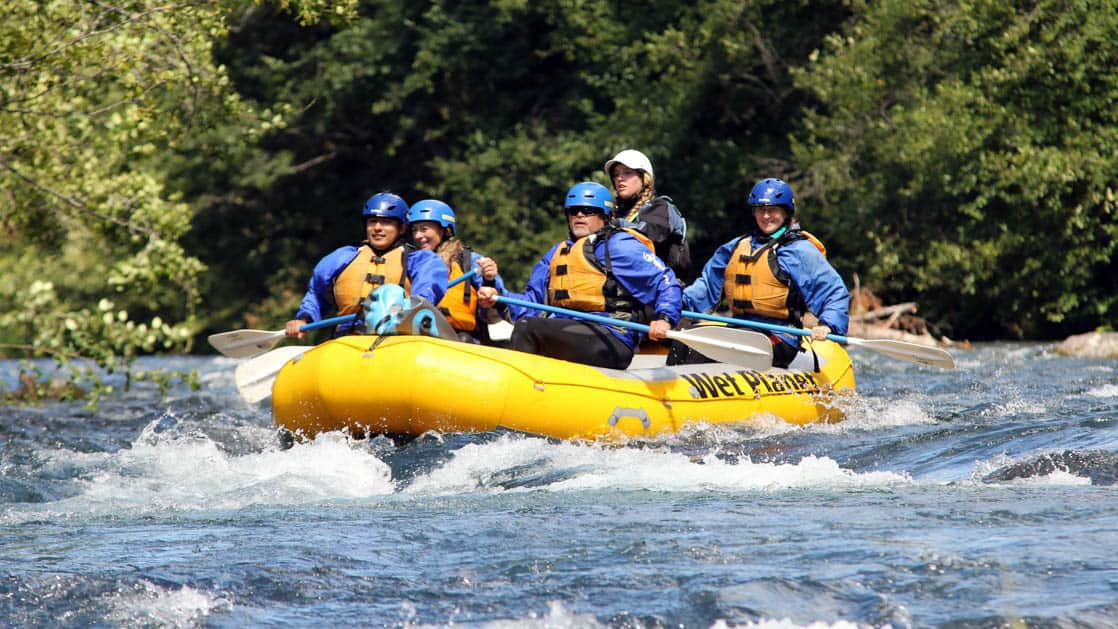 adventure travelers with blue helmets in a yellow raft going down rapids in the pacific northwest during the Rivers of Adventure & Wine small ship cruise trip