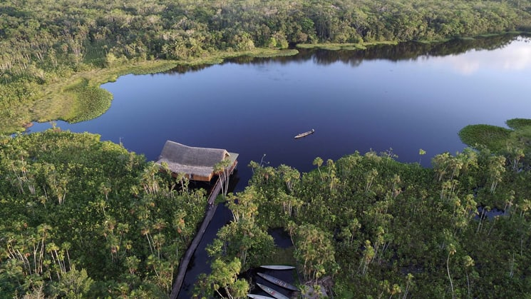 An aerial view of the Sacha Jungle Lodge, a sustainable hotel nestled in the Ecuadorian Amazon on the edge of a lake with 26 private thatched-roof cabins.