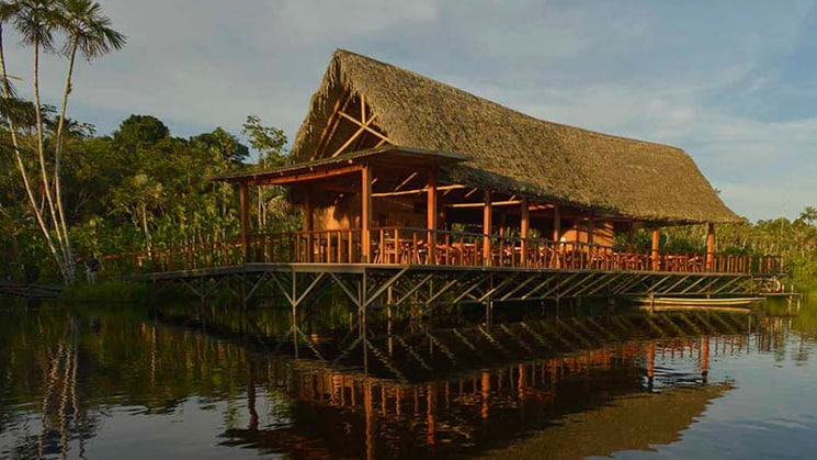 The main building at the Sacha Lodge, with a thatched roof and open-air porch, glows in the afternoon light of the Amazon and reflects in the still water.