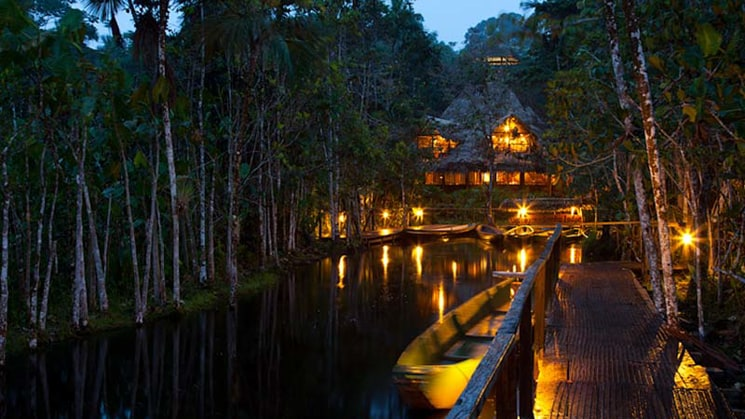Lights illuminate the Sacha Jungle Lodge at night, where guests experience a stay designed with nature in Ecuador's Amazon