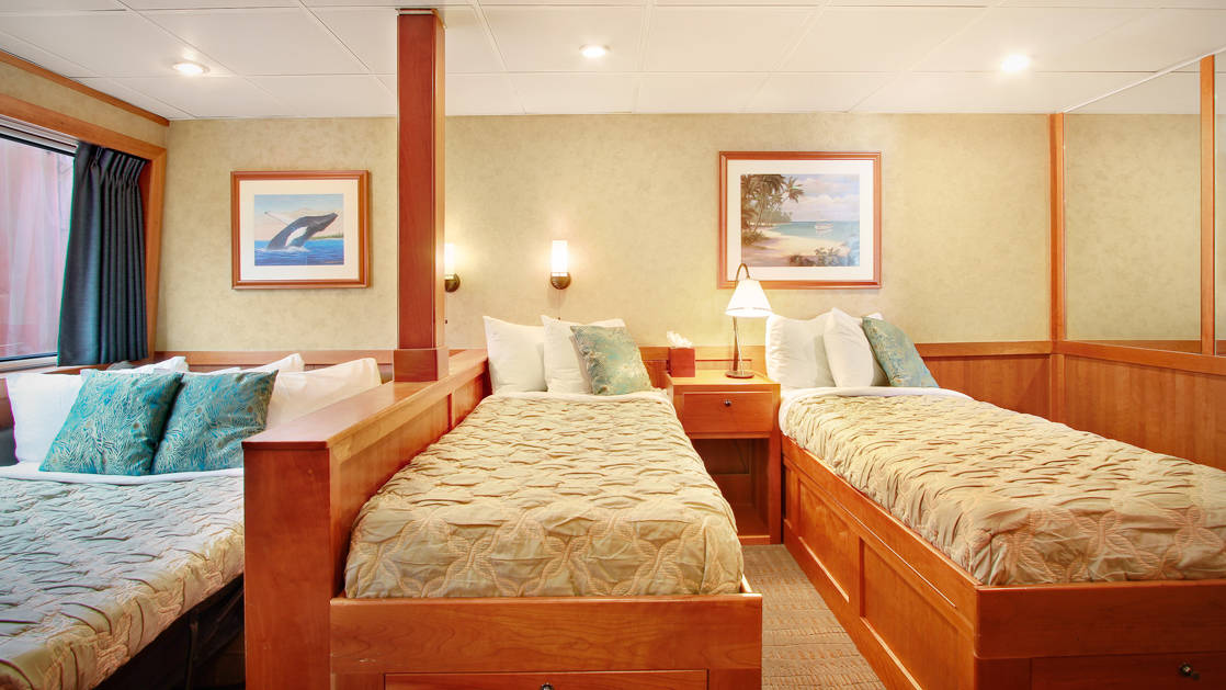 Admiral stateroom aboard the Safari Explorer Hawaii small ship, with three single beds and hanging pictures above the bed