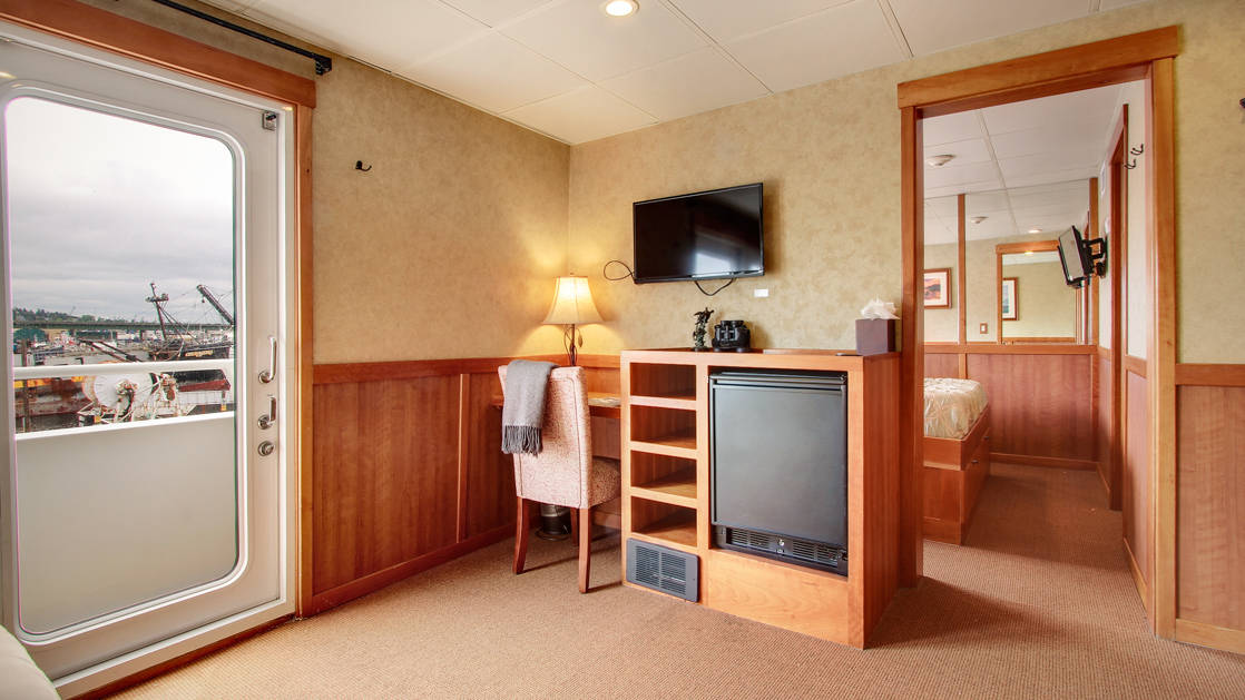 Seating area of commodore suite, wooden desk, with mini fridge, flat screen TV opening to adjoining room aboard the Safari Explorer Hawaii small ship