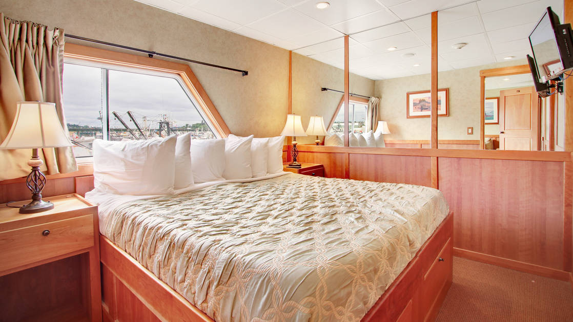 king bed with cream and white pillows on top of it and opening to adjoining room aboard the Safari Explorer Hawaii small ship