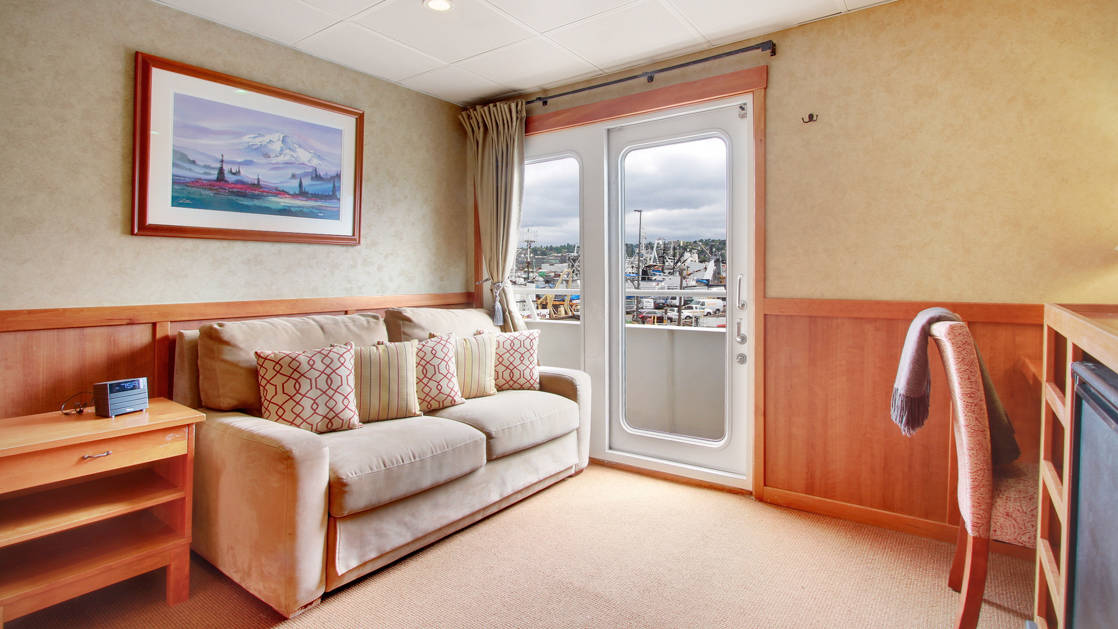 Seating area of commodore suite love seat, glass sliding doors, opening to adjoining room aboard the Safari Explorer Hawaii small ship