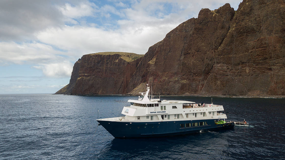 Safari Explorer Hawaii small ship cruising on a sunny day with large white clouds above.