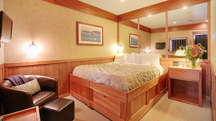 Jr Commodore stateroom with chair and foot stool with mirrors behind bed aboard the Safari Explorer Hawaii small ship
