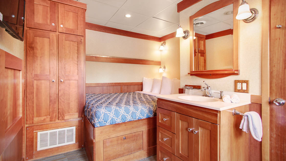 master stateroom with a large bed, nightstand and dresser aboard the Safari Explorer Hawaii small ship