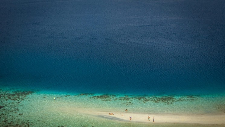 looking down at an indonesia beach at white sand, blue water and coral under the water