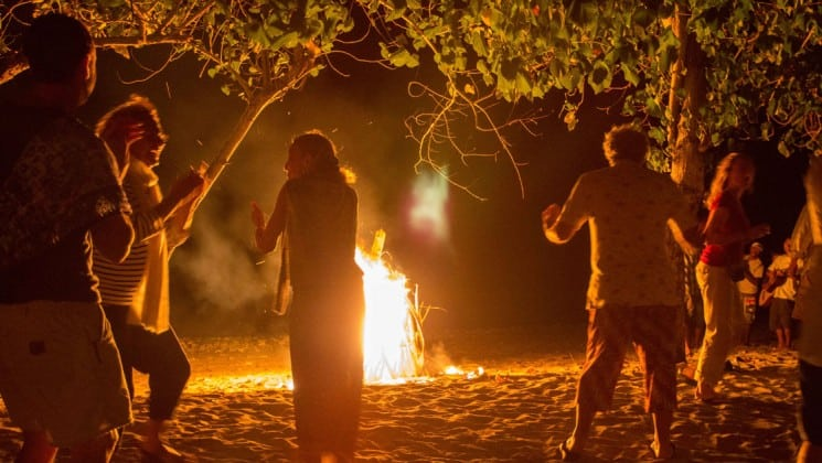 travelers socialize and dance around a bonfire on the beach at night in indonesia