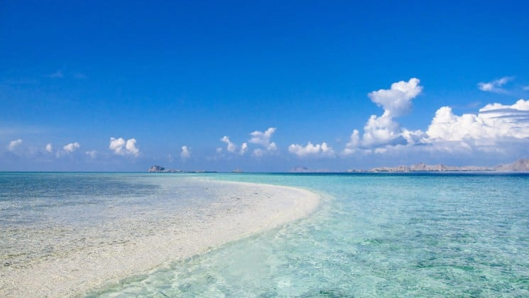 indonesia beach with clear water, blue skies and clouds above
