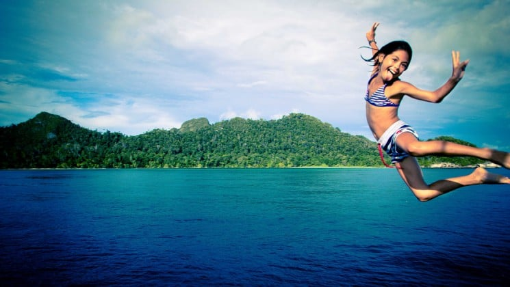 a young girl jumps off of the ombak putih small ship into turquoise water in indonesia with a green island in the background