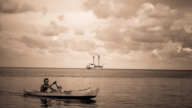 man and son canoeing on still water with the ombak putih small ship in the background with its sails down