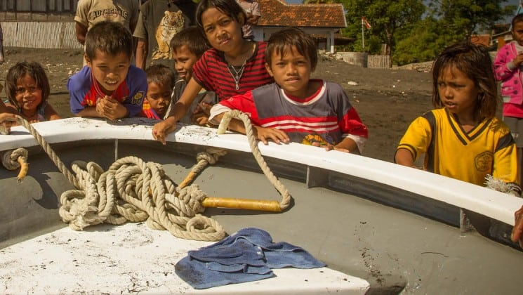 kids gathered around the bow of the ombak putih small ship on a sunny day in indonesia
