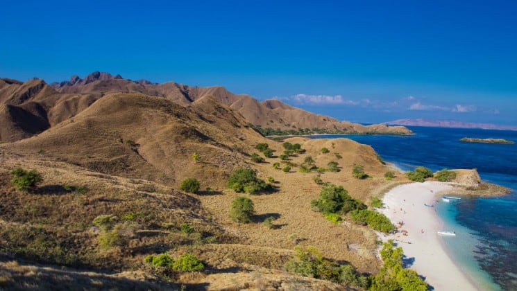 beach and mountainside in indonesia with blue water and blue sky on a sunny day
