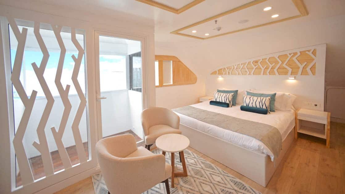 Main Deck Suite aboard Sea Star Galapagos small ship with white and cream decor, two chairs and table with balcony.