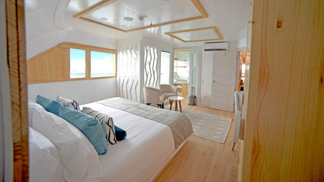 Main Deck Suite aboard Sea Star Journey. Bird's eye view of bed with balcony.