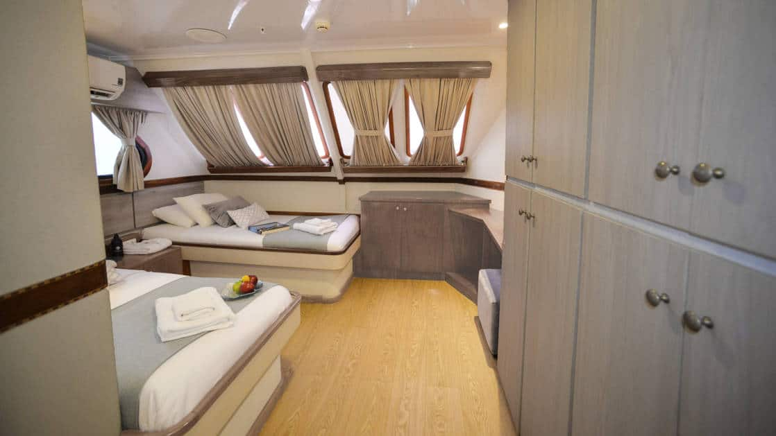 Two beds, nightstands and many windows in Standard Ocean View cabin aboard Seaman Journey in the Galapagos Islands